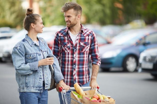 Casal com carrinho de compras no estacionamento