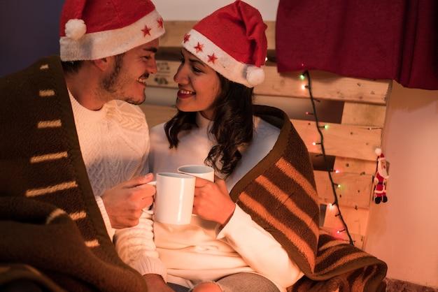 Casal com chapéus de natal olhando um para o outro segurando canecas em um ambiente rural com uma palete