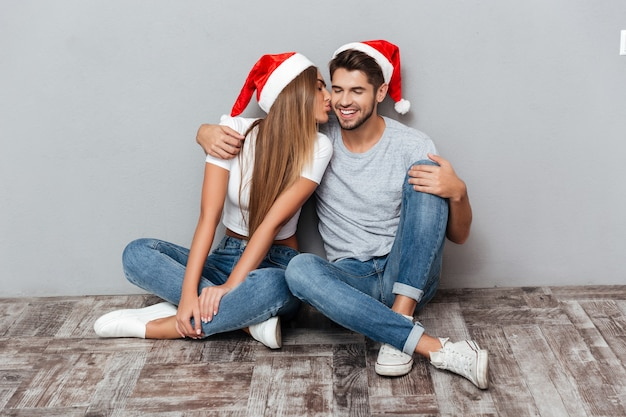 Casal com chapéus de natal se beijando