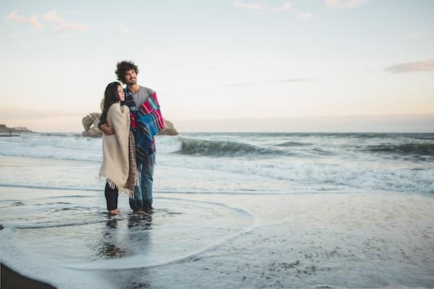 Casal com cobertores em cima e os pés na água da praia