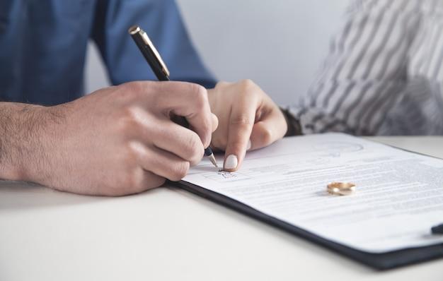 Casal com contrato de divórcio e anel na mesa. divórcio