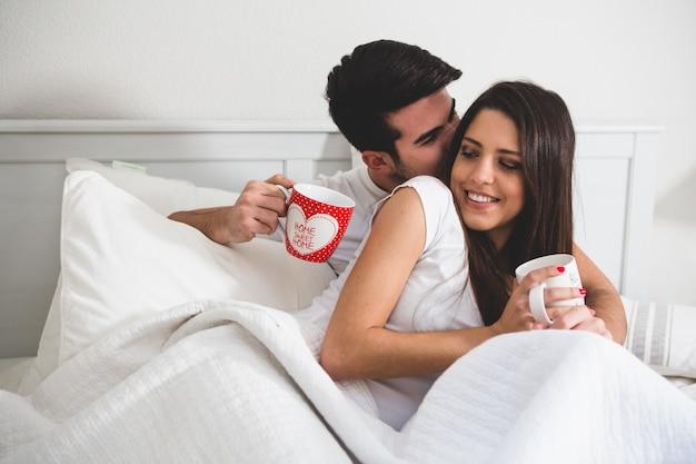 Casal com copos de café na cama