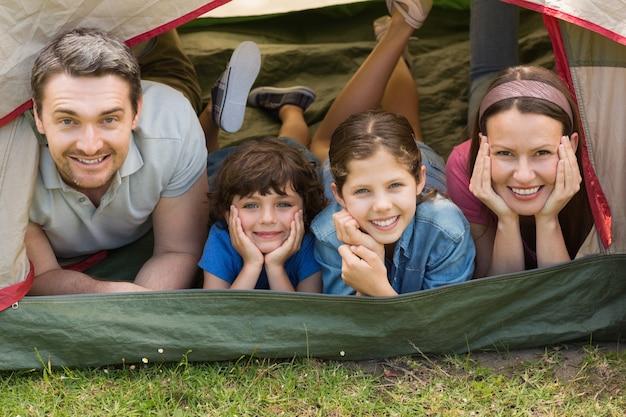 Casal com crianças deitada na tenda no parque