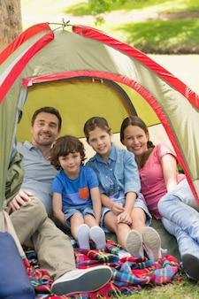 Casal com crianças sentadas na tenda no parque