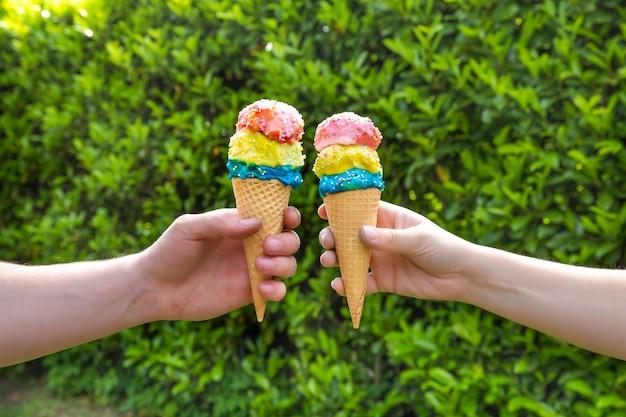 Casal com diferentes sabores coloridos de casquinha de sorvete com granulado com parede de folhas verdes