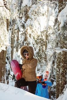 Casal com esqui e snowboard caminhando na montanha de neve