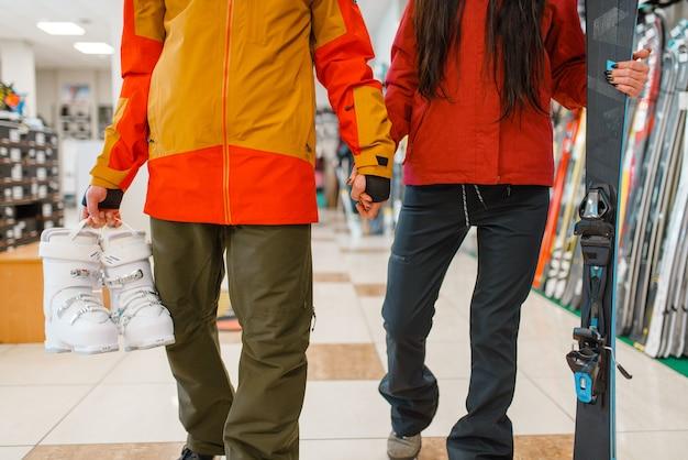 Casal com esquis e botas nas mãos, compras na loja de esportes. estilo de vida extremo na temporada de inverno, loja de lazer ativo, clientes comprando equipamentos de esqui