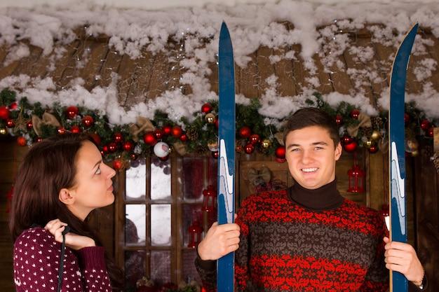 Casal com esquis em frente à cabana de madeira no inverno