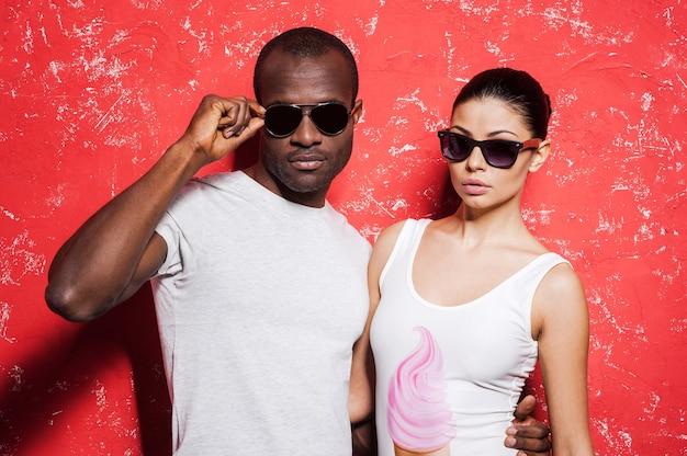 Casal com estilo. lindo casal jovem de raça mista em óculos de sol, em pé contra um fundo vermelho e olhando para a câmera