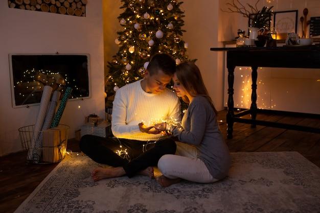 Casal com guirlanda de luz mágica nas mãos