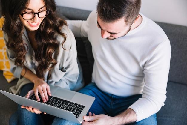 Casal com laptop no sofá em casa