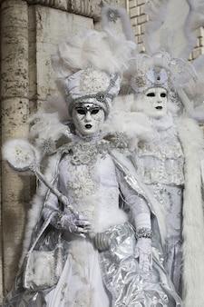 Casal com lindos vestidos e máscaras tradicionais de veneza durante o carnaval mundialmente famoso