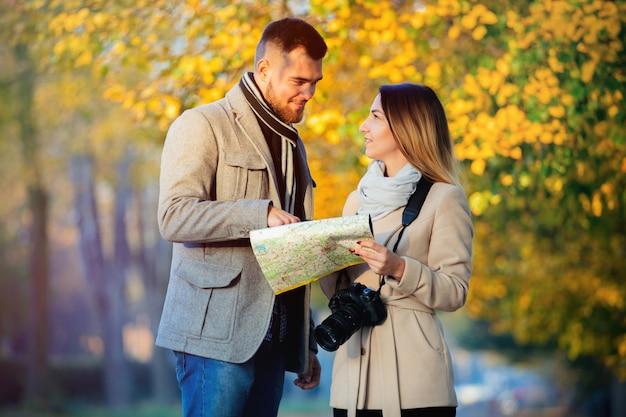 Casal com mapa e câmera no beco da cidade outono.