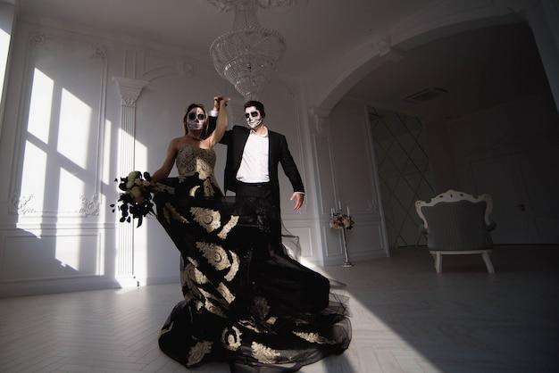 Casal com maquiagem de caveira escura sobre fundo branco. dia das bruxas