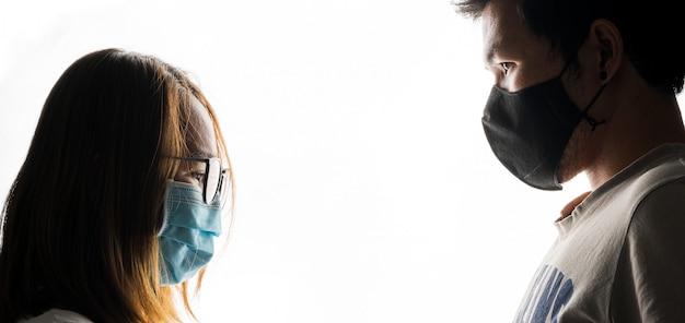Casal com máscara no fundo branco social distancing concept with space, covid-19 concept background
