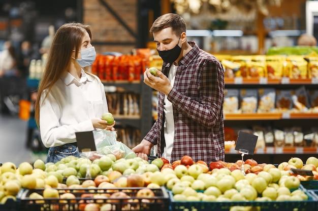 Casal com máscara protetora médica em um supermercado.