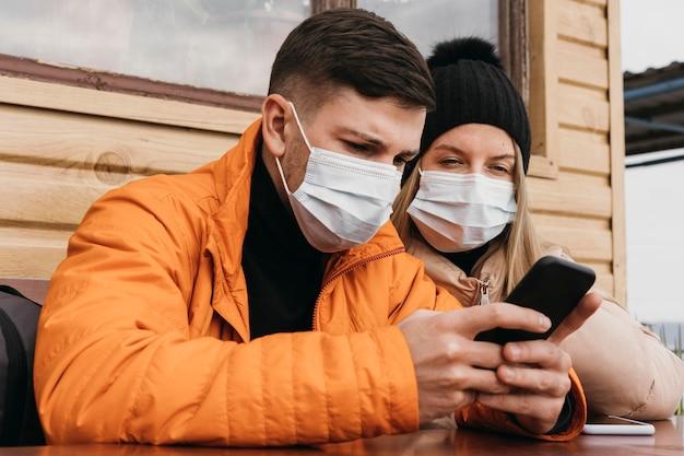 Casal com máscaras e smartphone