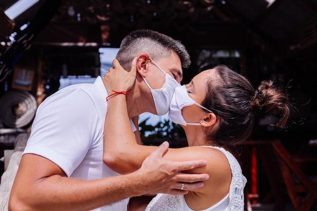 Casal com máscaras faciais brancas de férias em pé do lado de fora do hotel e se beijando