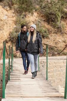 Casal com mochila caminhando na ponte