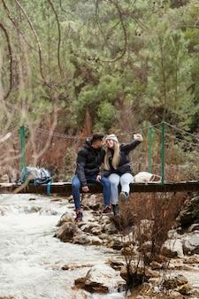 Casal com mochila sentado na ponte