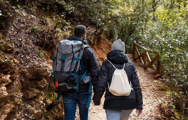 Casal com mochilas na natureza de perto