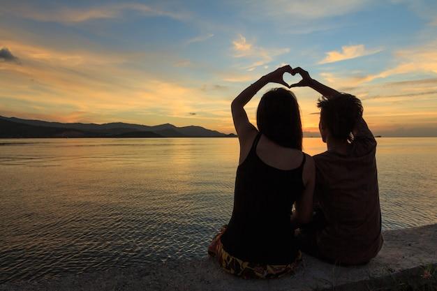 Casal com o símbolo do dedo do coração ao anoitecer