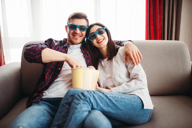 Casal com óculos 3d assistindo tv com pipoca