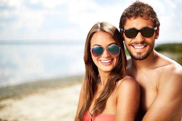 Casal com óculos de sol na praia
