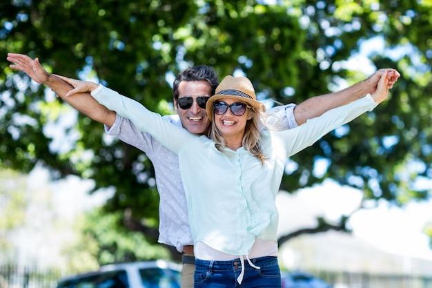 Casal com os braços estendidos em pé na rua