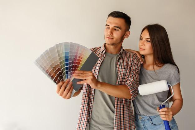 Casal com paleta de cores e rolo de pintura