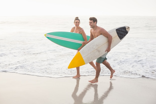 Casal com prancha correndo na praia