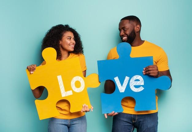 Casal com quebra-cabeças na mão sobre fundo azul claro. conceito de integração, união, relacionamento e parceria