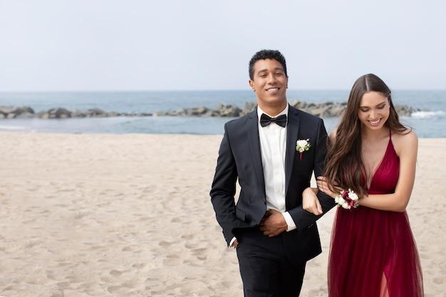 Casal com roupas de baile de formatura na praia