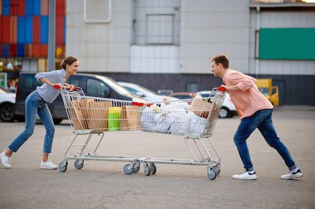 Casal com sacolas em carrinhos brinca sobre estacionamento