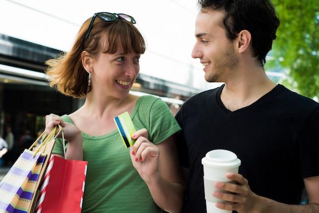 Casal com sacos de compras, andando nas ruas.