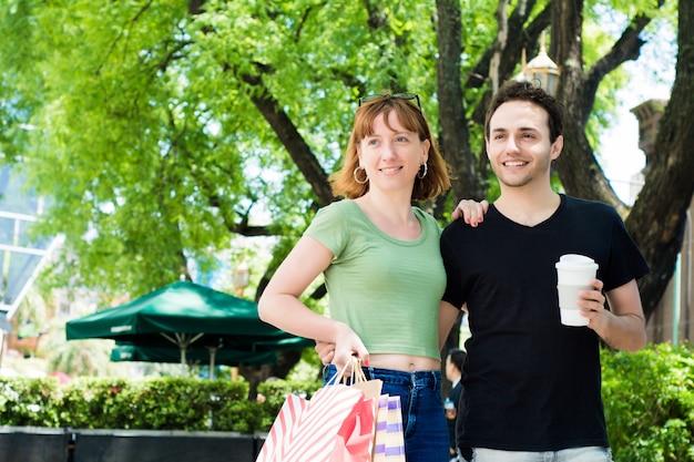 Casal com sacos de compras andando nas ruas.