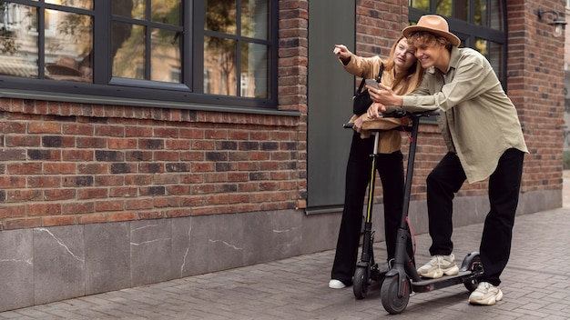 Casal com scooters elétricas ao ar livre