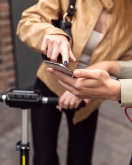 Casal com scooters elétricos verificando o smartphone ao ar livre
