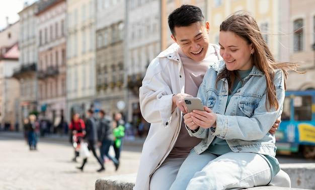 Casal com smartphone médio tiro