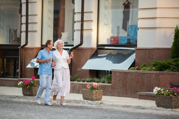 Casal com sorvete caminhando.
