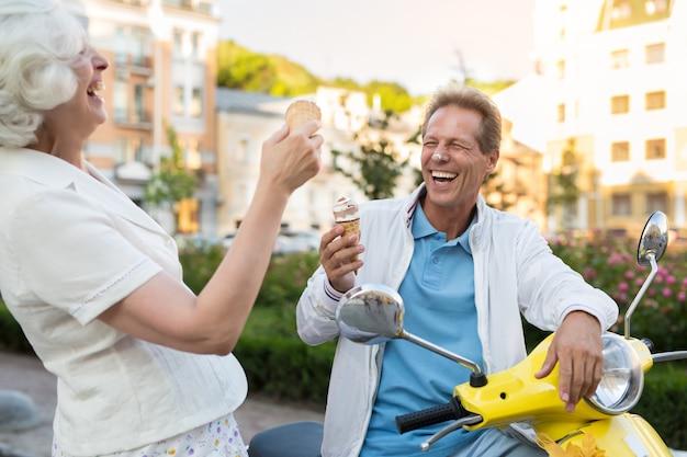Casal com sorvete rindo.
