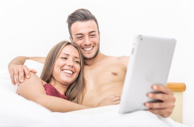 Casal com tablet na cama