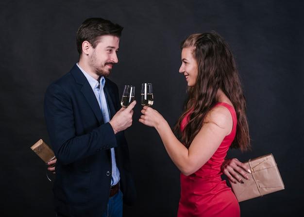 Casal com taças de champanhe escondendo presentes nas costas