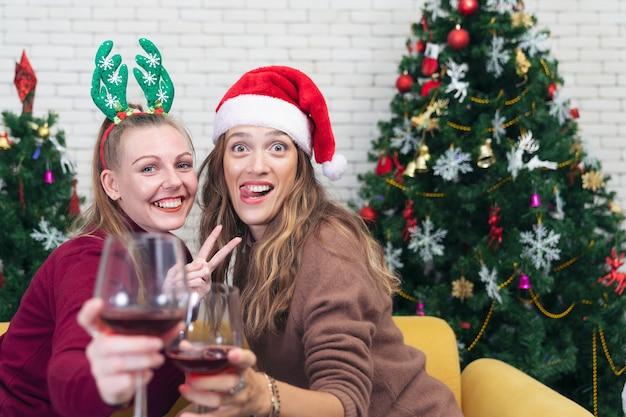 Casal com taças de vinho tinto perto da lareira. mulher jovem e bonita caucasiana com suéter e chapéu de papai noel na cabeça, sentada no sofá ao lado da árvore de natal