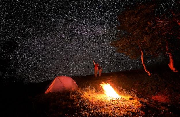 Casal com tenda junto a uma fogueira