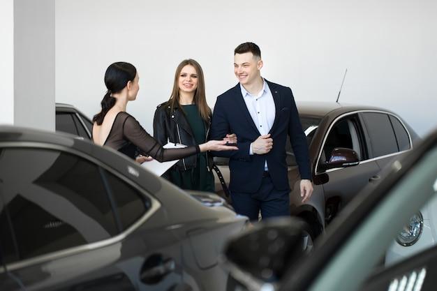 Casal com um negociante de carro em uma concessionária de carros