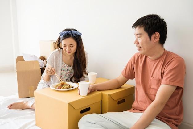 Casal come macarrão de pato assado em casa nova