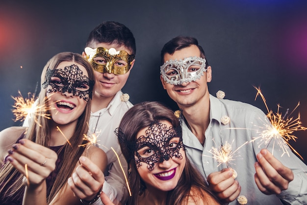 Casal comemorando a véspera de ano novo, bebendo champanhe e acendendo estrelinhas na festa de máscaras