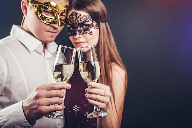 Casal comemorando a véspera de ano novo, bebendo champanhe na festa de máscaras