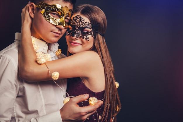 Casal comemorando a véspera de ano novo na festa de máscaras